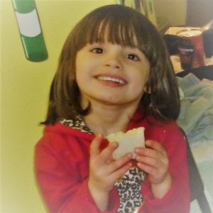 Image of a 3 year old girl enjoying her sandwich